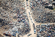 Trucks bring scrap from homes, cars, and other damaged items caused by Hurricane Katrina to a metal yard for recycling.