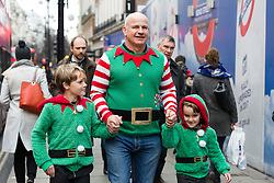 © Licensed to London News Pictures. 21/12/2016. London, UK. A man dressed as an elf with his two sons, dressed as his helpers, Christmas shopping in Oxford street in London, during the last week before Christmas. Photo credit : Vickie Flores/LNP