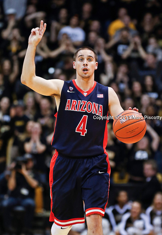 SHOT 2/26/15 8:42:47 PM - Arizona's T.J. McConnell #4 signals a play while dribbling the ball upcourt against Colorado during their regular season Pac-12 basketball game at the Coors Events Center in Boulder, Co. Arizona won the game 82-54.<br /> (Photo by Marc Piscotty / &copy; 2015)