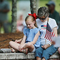 Yancey Harbour, 7, joins her grandmother, Pam, in prayer as attend Monday's Memorial Day service in Tupelo.