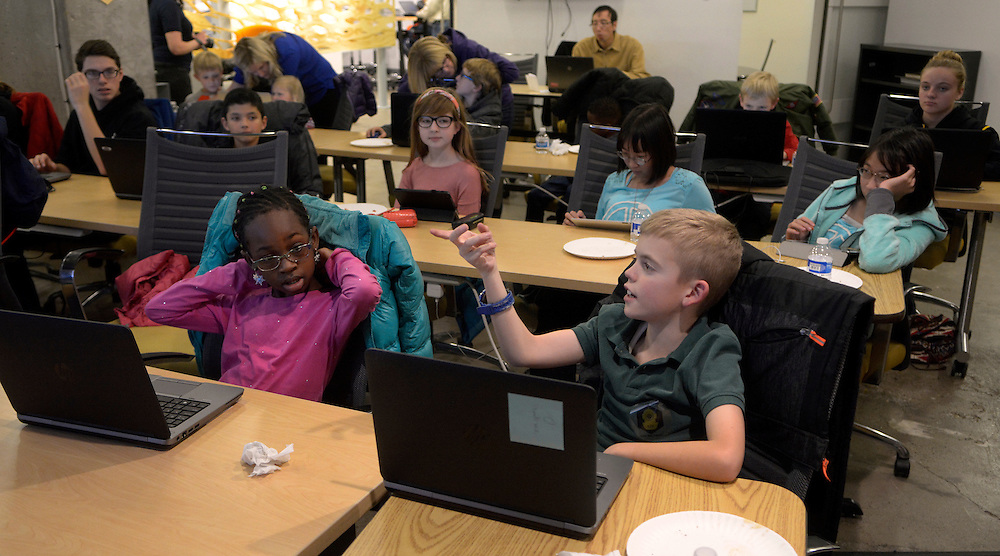 gbs120616r/ASEC -- Maggy Heckman, 8, left, of Albuquerque, listens to Evan Prior, 9, of Rio Rancho, right, make a point during The Hour of Code at the CNM Stemulus Center on Tuesday, December  6, 2016. The Hour of Code includes technology instruction to Elementary and middle school students who use block-progamming on their devices to create commands in a visual and fun way while learning the basic logic of coding. (Greg Sorber/Albuquerque Journal)