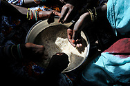 Young girls cleaning grains of semolina, a staple of the local diet. Global warming and climate change have caused prolonged drought and erratic rains across the Sahel in recent years, exacerbating food insecurity, hunger, poverty and altering traditional ways of life in the region. <br />