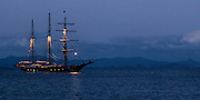 The Spirit of New Zealand at anchor in Hooks Bay, Waiheke Island. Photographed at dusk, with Coromandel Peninsula in the background.