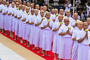 19 JULY 2014 - KHLONG LUANG, PATHUM THANI, THAILAND: Men who will be ordained as Buddhist monks participate in a procession around the ordination hall at Wat Phra Dhammakaya. Seventy-seven men from 18 countries were ordained as Buddhist monks and novices at Wat Phra Dhammakaya, a Buddhist temple  north of Bangkok, Saturday. It is the center of the Dhammakaya Movement, a Buddhist sect founded in the 1970s and led by Phra Dhammachayo (Phrathepyanmahamuni). It is the largest temple in Thailand. The Dhammakaya sect has an active outreach program that attracts visitors from around the world.    PHOTO BY JACK KURTZ
