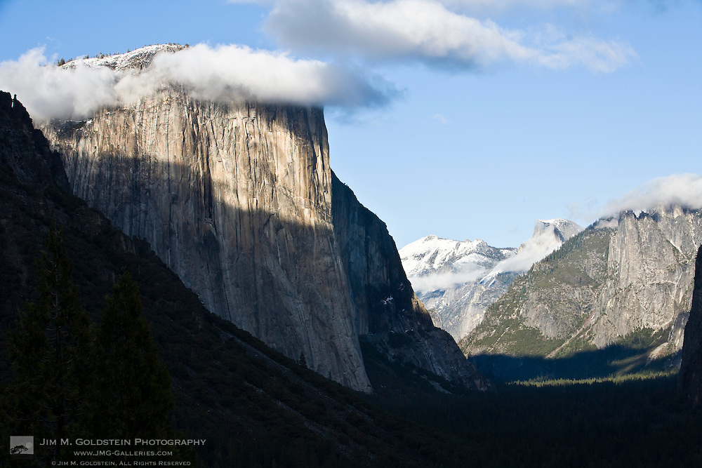 Clouds form around the peak of El Capitan as afternoon light paints Yosemite Valley, Yosemite National Park, California
