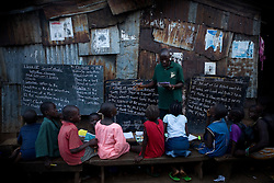 A class is taught in a narrow passage in Kroo Bay slum..Kroo Bay, Freetown, Sierra Leone.