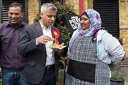 © Licensed to London News Pictures. 30/05/2015. London, UK. Sadiq Khan eating some Asian snacks at a local public event as he joins Labour Party activists in Stepney, Tower Hamlets in east London to support canvassing for John Biggs to become Tower Hamlets Mayor. The Tower Hamlets Mayoral election will be re-run on 11th June after a High Court election petition found the previously elected mayor, Lutfur Rahman guilty of corrupt and illegal practices. Photo credit : Vickie Flores/LNP