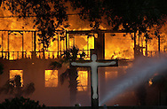 TAMPA,FL. - FIRE- A cross at Lady of Perpetual Hope sits in the foreground as an apartment complex under construction burns in Ybor City Friday. The fire started when a forklift touch electrical wires. It went up like logs on a bonfire. When flames licked the wooden frames of the apartments in The Park at Ybor City, it touched off a blaze that quickly destroyed the apartment complex and, a short time later, a nearby post office. Firefighters battled the inferno - and their exhaustion - for hours. When it was over, five city blocks were leveled at a cost of about $40 million. ( Ybor City Inferno - Camden Property Trust - Apartments , Six-Alarm Fire )   ..SCOTT ISKOWITZ - TRIBUNE PHOTO