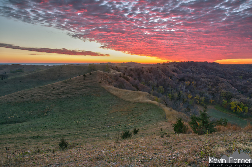 Colorful clouds light up the sky over the Loess Hills at dawn. On this morning, the best colors happened before the sunrise, the sun came out for a few minutes, and then the light went flat as it went behind the clouds. This view is from the top of Murray Hill.