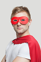 Portrait of young man wearing superhero costume against gray background