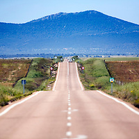 Lonesome road in province of Caceres, Spain. Straight road leading to mountains with single car in distance.