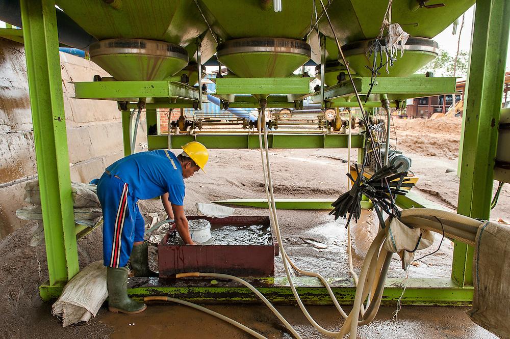 Worker checks tin sand in the Pemali mine, the biggest legal mine in Bangka that has completely devastated the once green landscape.. Operated by PT-Timah. It produces 60 tons of tin per month. Indonesia is the worlds biggest tin provider, vital for assembling smart phones and other electronic products.  Bangka Island (Indonesia) is devastated by tin mines. The demand for tin has increased due to its use in smart phones and tablets.<br /> <br /> Mineur vérifie l'étain dans la  Mine de Pemali, plus grande mine légale de Bangka. Exploité par PT-Timah. Elle produit 60 tonnes d'étain par mois. L'île de Bangka (Indonésie) est dévastée par des mines d'étain. La demande de l'étain a explosé à cause de son utilisation dans les smartphones et tablettes Réparation d'une station de pompage d'eau. Mine de Pemali, plus grande mine légale de Bangka. Exploité par PT-Timah. Elle produit 60 tonnes d'étain par mois. L'île de Bangka (Indonésie) est dévastée par des mines d'étain. La demande de l'étain a explosé à cause de son utilisation dans les smartphones et tablettes.