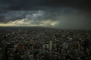 Storm front from one of three typhoons converging that day on the Tokyo megalopolis sends sheets of rain down on the city.  Climate scientist say that rare, severe weather events will be more common in the age of global warming.   Shinjuku, Tokyo, Japan.