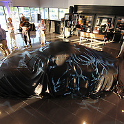 A 2014 Porsche Cayman S sits in the middle of the showroom covered during a Porsche Cayman S Unveiling Thursday, May. 2, 2013, at  Porsche of Delaware in Newark Delaware.