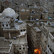 Yemenis walk through the narrow steets of Old San'aa at dusk. UNESCO, the United Nations cultural organization, declared San'a a world heritage site in 1988. San'a was a trade capital as early as the 1st century B.C. With merchants crowded  inside the mud walls of the city, the San'anis built upwards -- as high as nine stories, an impressive feat given the technology of the time. San'aa's homes rest on lower stories built of stone; some date to the 9th or 10th centuries. Over generations, families added floors in brick, making each new floor slightly smaller than the previous one for stability.