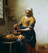 The Servant' also called 'The Milkmaid' or 'The Kitchen Maid' c1660. Oil on canvas.  Jan Vermeer (1632-1675) Dutch Baroque painter. Young woman standing at table beneath a window pours milk into a bowl. Basket Bread Food Jug Tankard