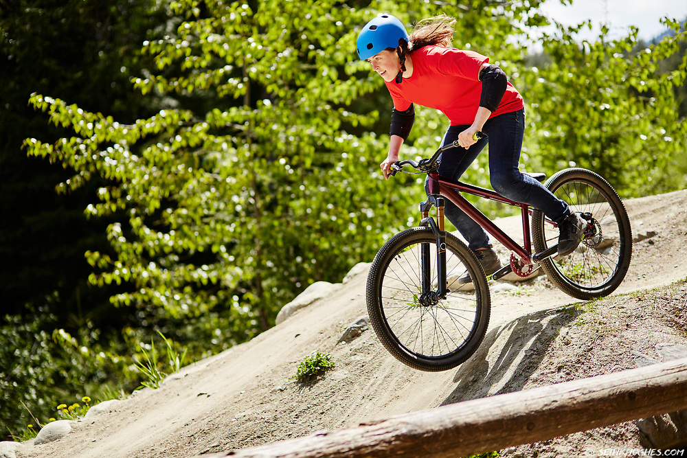 A girl on her bicycle dropping in to the dirt jumps at Whistler, British Columbia