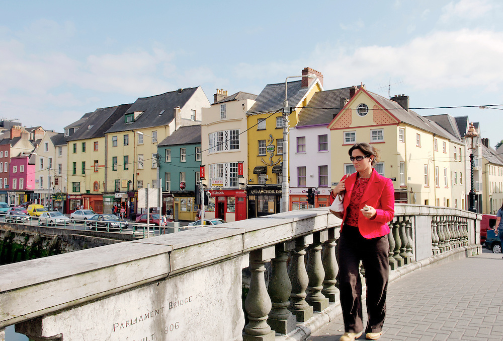 Cork City Ireland young business woman crossing Parliament Bridge on the River Lee with old warehouses on Georges Quay behind.