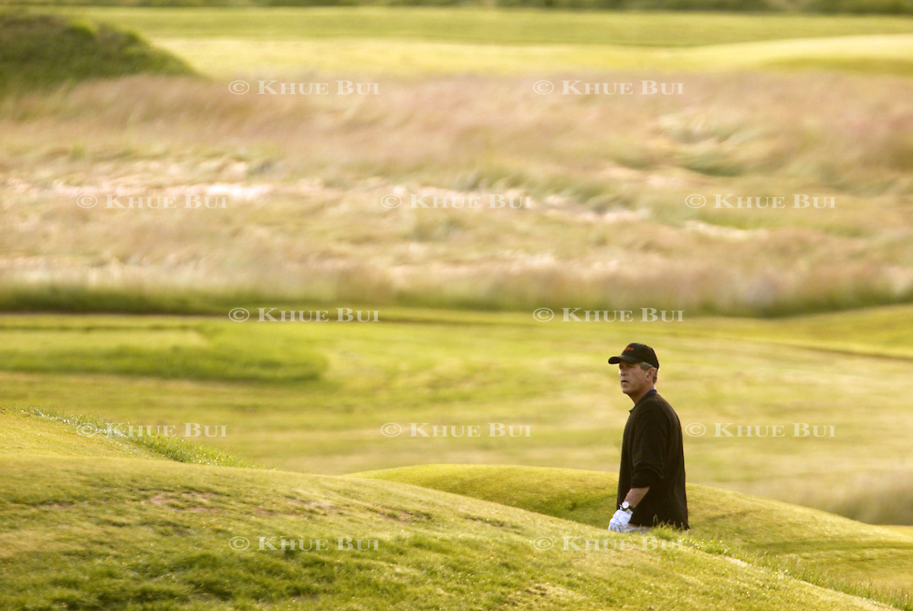 President Bush looks for the flag while hitting out of a bunker during morning golf Saturday, July 6, 2002, in Kennebunkport, Maine.  President Bush is spending the Independence Day weekend in Kennebunkport, Maine, home of his parents...Photo by Khue Bui
