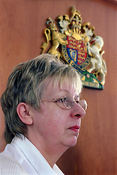 Portrait of female magistrate listening to case of young offender in youth court,