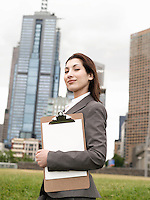 Young woman with clipboard outside office building