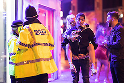"""© Licensed to London News Pictures . 17/12/2016 . Manchester , UK . A man carries a woman on his back along Withy Grove . Revellers out in Manchester City Centre overnight during """" Mad Friday """" , named for being one of the busiest nights of the year for the emergency services in the UK . Photo credit : Joel Goodman/LNP"""