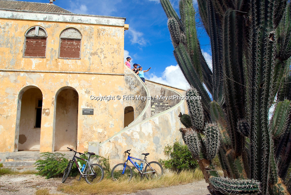 Jan Thiel, Curacao, Netherlands Antilles, April 2009. The Quarantaine building. Mountainbiking is the perfect way to explore Curacao. Ellemieke van Beek of Wannabike tours guides a small group of bikers through the rugged nature of Jan Thiel Lagoon. Jan Thiel lagoon, located on the southeast side of the island, is a very popular area for local mountain bikers of all levels..The area is one of the most unique nature reserves on Curacao characterized by its rare vegetation, exceptional bird life, and unspoiled views. The island has a lot more to offer than sun, sea, and beaches! However, the best spots are hard to find without a guide, even with a map