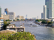 20 APRIL 2013 - BANGKOK, THAILAND:  Boats on the Chao Phraya River as seen from the River Vibe restaurant in Talat Noi (Talat means Market, Noi means Small. Literally Small Market). The Talat Noi neighborhood in Bangkok started as a blacksmith's quarter. As cars and buses replaced horse and buggy, the blacksmiths became mechanics and now the area is lined with car mechanics' shops. It is one the last neighborhoods in Bangkok that still has some original shophouses and pre World War II architecture. It is also home to a  Teo Chew Chinese emigrant community.   PHOTO BY JACK KURTZ