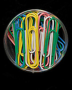 large colorful paperclips in a little container on a black background