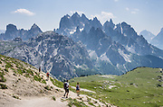 "Hikers admire sharp peaks of the Cadini Group in the Sesto Dolomites, Veneto region, Italy, Europe. In the Cadini di Misurina, Cima Grande rises to 2999 meters (9839 feet), between Cima Piccola and Cima Ovest. The Cadini Group is in the municipality of Auronzo, in the Sesto Dolomites (Dolomiti di Sesto, or Sexten/Sextner/Sextener Dolomiten) which lie north of the Fiume Ansiei valley. From the Rifugio Auronzo toll road, hike for spectacular views around Tre Cime di Lavaredo (Italian for ""Three Peaks of Lavaredo,"" called Drei Zinnen or ""Three Merlons"" in German). The Dolomites are part of the Southern Limestone Alps. UNESCO honored the Dolomites as a natural World Heritage Site in 2009."