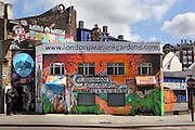 Three guys talking at the corner and in the shade of a spray paint graffiti building located 24 Great Eastern Street in London, UK. Picture by Manuel Cohen