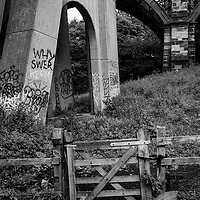 Large bridge and fence with gate and graffiti