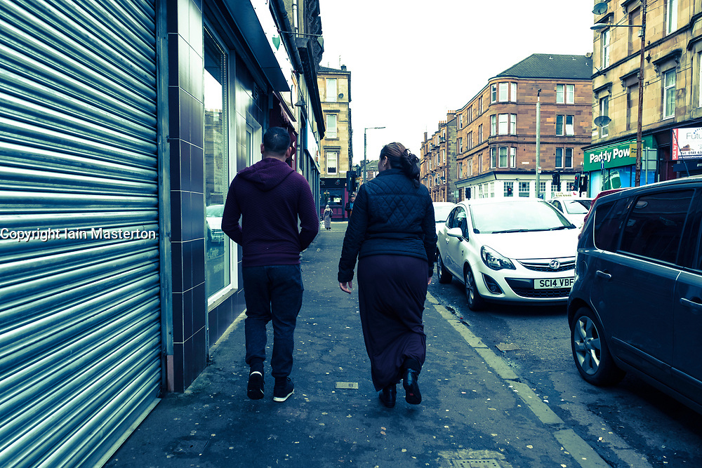 Roma couple walking on streets of Govanhill in Glasgow, Scotland, United Kingdom