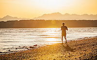 A young man running on a beach in Seattle's Discovery Park. Seattle, Washington, USA.