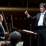 """November 21, 2013 - New York, NY : Conductor Alan Gilbert, standing at right, leads the New York Philharmonic and tenor Michael Slattery, standing at left, in Bejamin Britten's """"Serenade for Tenor, Horn, and Strings, Op. 31 (1943)"""" at Avery Fisher Hall at Lincoln Center on Thursday night. Slattery made his NY Phil debut as a last-minute substitution for tenor Paul Appleby, who withdrew due to illness. CREDIT: Karsten Moran for The New York Times"""