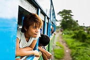 15 JUNE 2013 - YANGON, MYANMAR:  Passengers lean out of the windows of the Yangon Circular Train. They Yangon Circular Railway is the local commuter rail network that serves the Yangon metropolitan area. Operated by Myanmar Railways, the 45.9-kilometre (28.5 mi) 39-station loop system connects satellite towns and suburban areas to the city. The railway has about 200 coaches, runs 20 times and sells 100,000 to 150,000 tickets daily. The loop, which takes about three hours to complete, is a popular for tourists to see a cross section of life in Yangon. The trains from 3:45 am to 10:15 pm daily. The cost of a ticket for a distance of 15 miles is ten kyats (~nine US cents), and that for over 15 miles is twenty kyats (~18 US cents). Foreigners pay 1 USD (Kyat not accepted), regardless of the length of the journey.     PHOTO BY JACK KURTZ