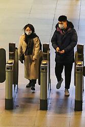© Licensed to London News Pictures. 06/03/2020. London, UK. Members of public wearing protective face mask at  Canary Wharf ticket barrier. On Thursday 5 March a woman in her 70s with underlying health condition become the first person in the UK to die from coronavirus. 116 cases in the UK have tested positive of the virus. Photo credit: Dinendra Haria/LNP