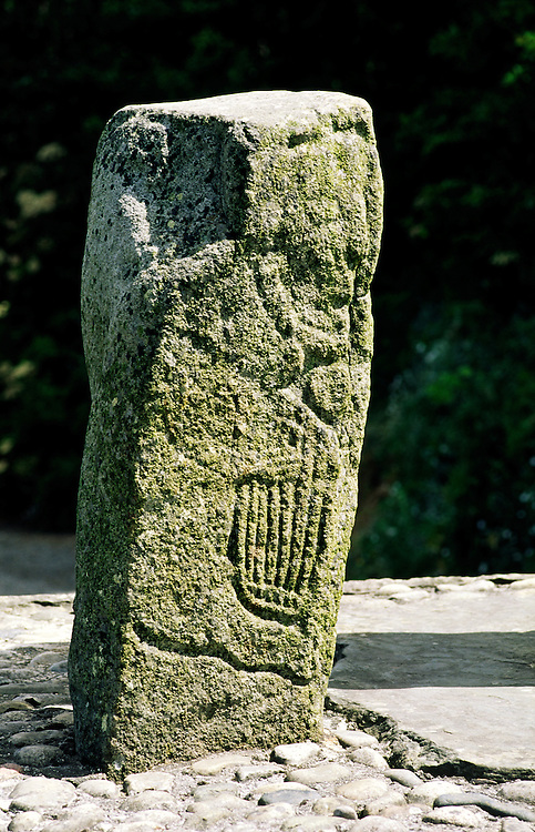 Man playing Celtic clarsach harp on one of 2 carved stones flanking the early Christian Carndonagh Cross, Co. Donegal, Ireland.