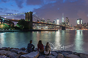 Three young adults watch sunset over the Brooklyn Bridge and the Manhattan sklyine light up as night falls in New York City.