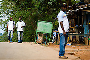 HIV/AIDS counselor Kevin Kouassi Gallet walks alongside Dr. Charles Joseph Diby down a street in Dimbokro, Cote d'Ivoire on Friday June 19, 2009.