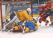 Lake Superior State Laker goal tender Kevin Kapalka (30) gets taken down as players charge the net during round one of the CCHA playoffs at Taffy Abel Arena.