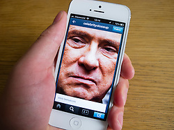 Silvio Berlusconi face on Tumblr social media and photo on white iPhone 5 smartphone