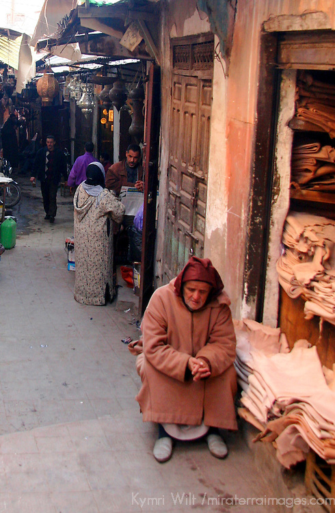 North Africa, Africa, Morocco, Marrakesh.  Elderly Moroccan tends souk.