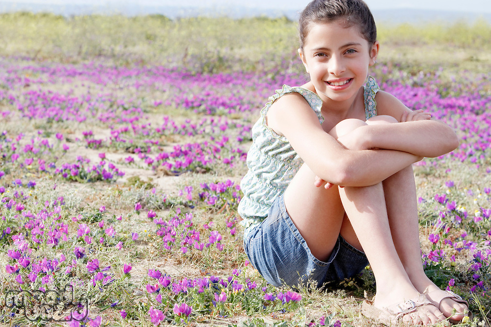 Smiling Girl sitting arms around folded legs in Field of Flowers