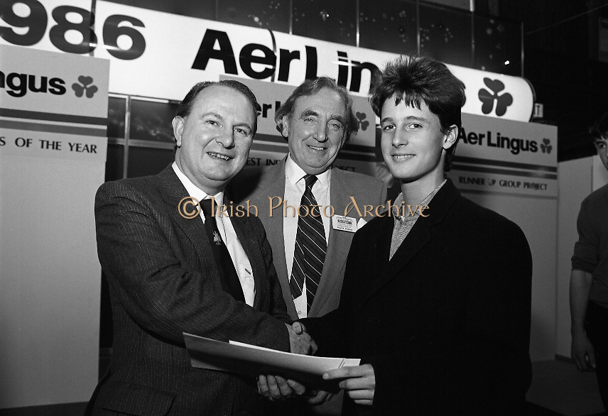 "Aer Lingus Young Scientist Exhibition..1986..10.01.1986..01.10.1986..10th January 1986..The annual Aer Lingus,sponsored,Young Scientists Exhibition was held at the RDS,Ballsbridge,Dublin.The Overall winners of the competition were Ms Breda Maguire and Ms Niamh Mulvany..They are students at The Rosary College,Raheny,Dublin. The Tanaiste, Mr Dick Spring TD was on hand to present the awards...Picture shows Mr Con Power,Director Economic Policy,Conferation Of Irish Industry presenting the CII award for Physical,Mathematical and applied Sciences (Senior Pupils) to Colman Byrnes.Colman, of the Methodist College, Belfast submitted a project entitled ""The Eight Directional Joystick. Also in the picture is Mr Niall G Weldon, Chairman of the judging panel."