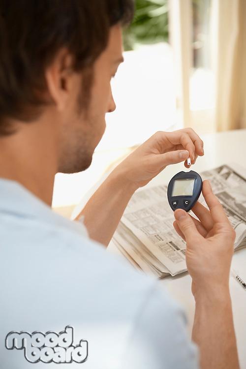 Man Using Blood Sugar Meter in living room