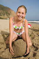 Girl Playing in Sand at Beach