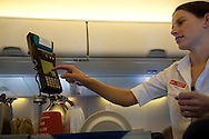 a female flight attendant serves meals and drinks for purchase aboard a Virgin Blue flight in Australia