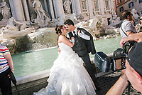 """ROME, ITALY - 20 JUNE 2017: A just married couple poses for a picture for their wedding photographer by the Trevi Fountain in Rome, Italy, on June 20th 2017.<br /> <br /> The warm weather has brought a menacing whiff of tourists behaving badly in Rome. On April 12, a man went skinny-dipping in the Trevi fountain resulting in a viral web video and a 500 euro fine.<br /> <br /> Virginia Raggi, the mayor of Rome and a national figurehead of the anti-establishment Five Star Movement,  issued an ordinance involving harsher fines for eating, drinking or sitting on the fountains, for washing animals or clothes in the fountain water or for throwing anything other than coins into the water of the Trevi Fountain, Bernini's Four Fountains and 35 other city fountains of artistic or historic significance around the city.  """"It is unacceptable that someone use them to go swimming or clean themselves, it's an historic patrimony that we must safeguard,"""" Ms. Raggi said."""