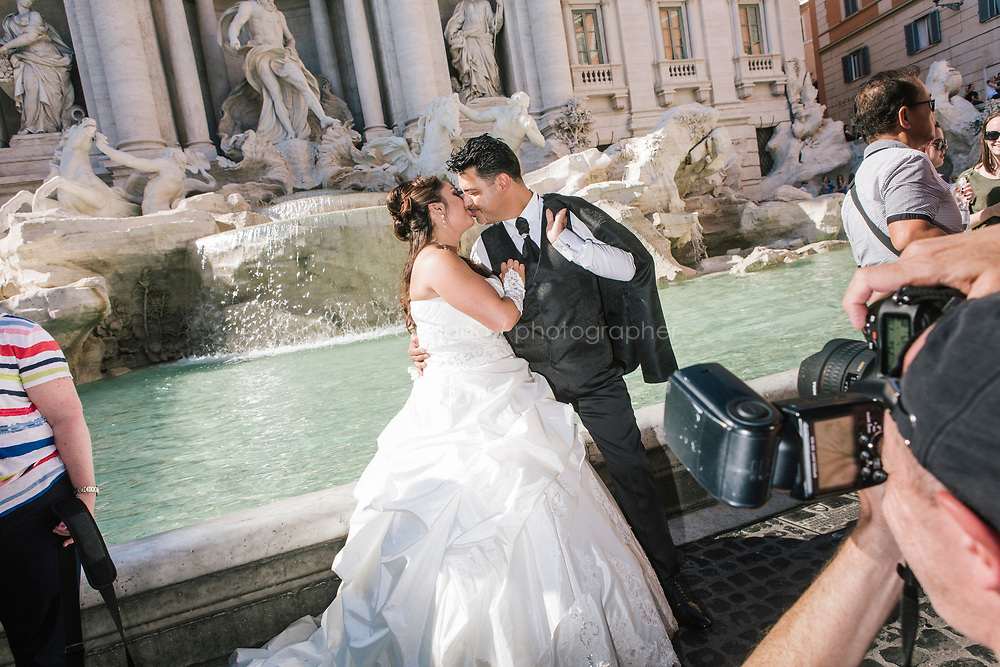 ROME, ITALY - 20 JUNE 2017: A just married couple poses for a picture for their wedding photographer by the Trevi Fountain in Rome, Italy, on June 20th 2017.<br /> <br /> The warm weather has brought a menacing whiff of tourists behaving badly in Rome. On April 12, a man went skinny-dipping in the Trevi fountain resulting in a viral web video and a 500 euro fine.<br /> <br /> Virginia Raggi, the mayor of Rome and a national figurehead of the anti-establishment Five Star Movement,  issued an ordinance involving harsher fines for eating, drinking or sitting on the fountains, for washing animals or clothes in the fountain water or for throwing anything other than coins into the water of the Trevi Fountain, Bernini&rsquo;s Four Fountains and 35 other city fountains of artistic or historic significance around the city.  &ldquo;It is unacceptable that someone use them to go swimming or clean themselves, it&rsquo;s an historic patrimony that we must safeguard,&rdquo; Ms. Raggi said.